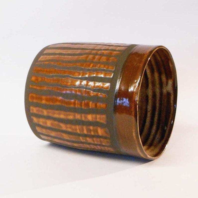 Wheel thrown black noir clay with Orange stripes.