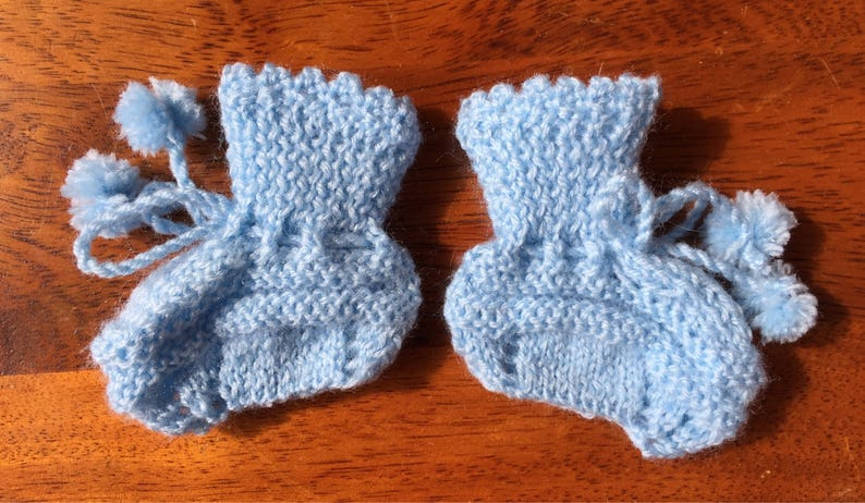 Hand knit baby booties with pompoms