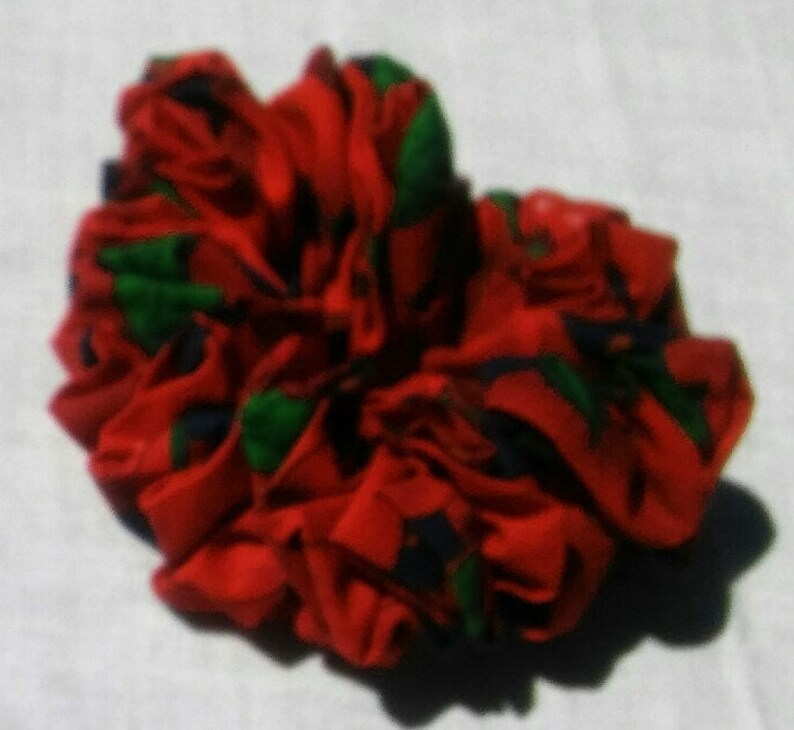 Two different cotton schrunchies One regular maroon with orange and black cotton schrunchie. One large apple design with red background