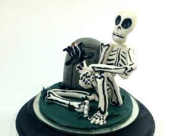 Clarence is a polymer clay skeleton monster holding a glass eyeball flower sitting on a wooden base and looking for a home