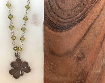 Lucky 4 leaf clover hanging from wirewrapped green cubic zirconia sterling silver chain