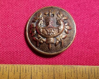 Single large brass coat button with coat of arms
