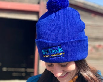 SoDak is for Ranchers Embroidered Blue Pom Pom Beanie - South Dakota is for Ranchers Blue Beanie Winter Hat by Oh Geez! Design - Ranching