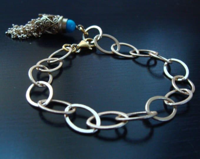 Gold charm bracelet with tassel charm