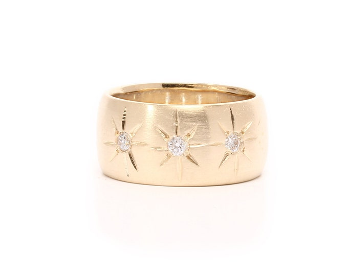 Gold cigar band ring with three diamonds and starburst engraving celestial stars