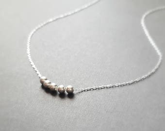 Simple, tiny, sterling silver necklace with 5 small beads
