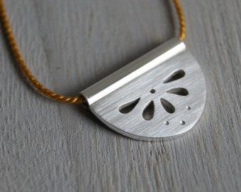 Mandala, a silver silhouette pendant, cut and pierced, argentium silver, silk, yellow, wedge