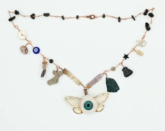 Curio Cabinet on a Charm Necklace with Blue-Green Winged Prosthetic eye Centerpiece and Obsidian Beads