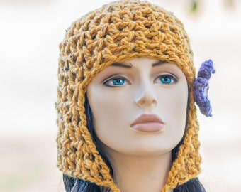 Cleo's New Hat - mustard yellow, crocheted beanie hat with ear flap and chin ties removeable flower hair clip. Cleopatra's wig bob hair cut.