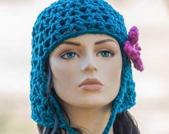 Cleo's New Hat - turquoise, crocheted beanie hat with ear flap and chin ties removeable flower hair clip. Cleopatra's wig bob hair cut.