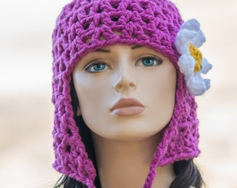 Cleo's New Hat - pink, crocheted beanie hat with ear flap and chin ties removeable flower hair clip. Cleopatra's wig bob hair cut.