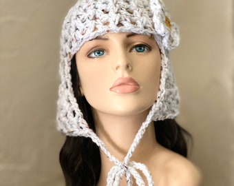 Cleo's New Hat - natural white tweed, crocheted hat with ear flap and chin ties removeable white flower clip. Cleopatra's wig bob hair cut.