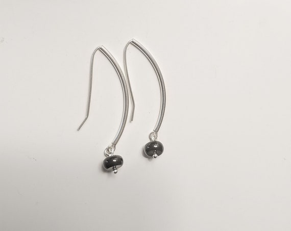 Black Onyx disc dangle earrings.  Discs hang from curved sterling silver tubes with self made earwires.  Lightweight,