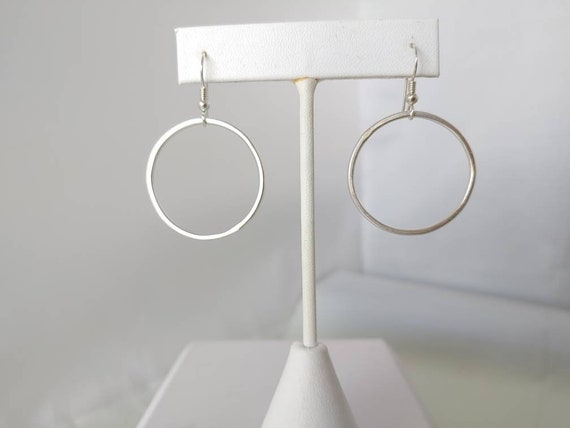 "Dangling Hoop on French wires. Flattened round sterling wire hang from earwires. 1 1/4"" drop. 1 1/4"" wide."