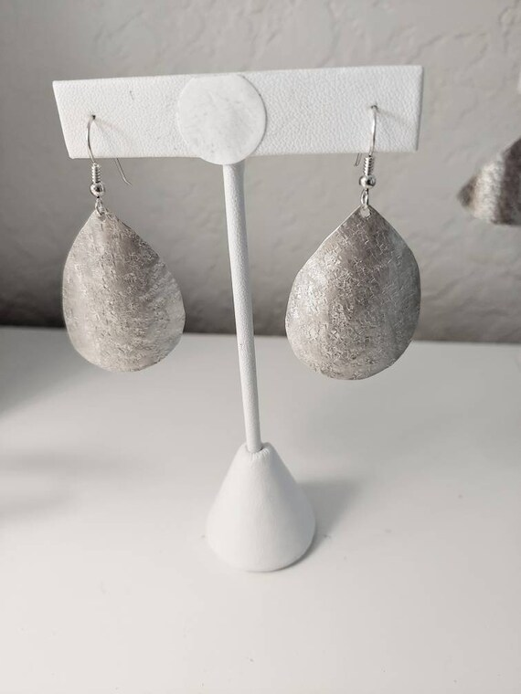 Sterling raw silk textured teardrop earrings dangle from french wires.