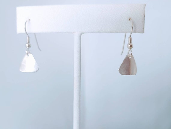 Lightly brushed small triangle drop earrings dangle from french wires.