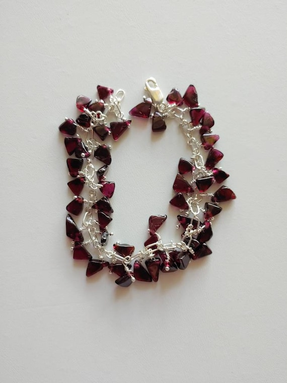 Oh the feel of silver!!! 50 garnet chips charm their way around this sterling link bracelet. All individually wire wrapped. Adjustable.