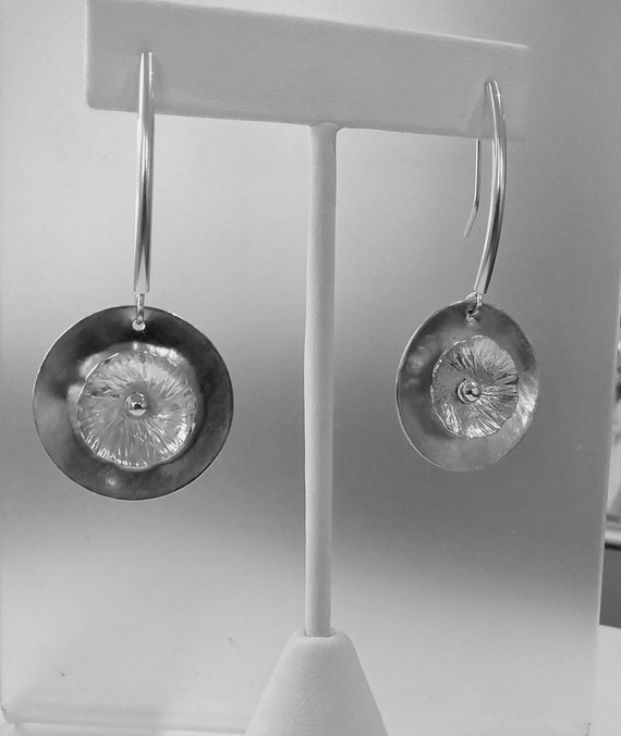 Textured sterling flower dangle earrings.  Discs hang from sterling silver tubes with self made earwires.  Total length approximately 2.25""