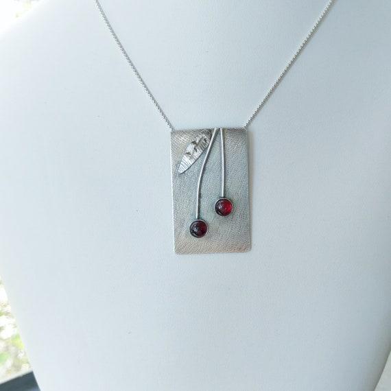 "Garnet stones (6mm) set in sterling pendant on sterling bail on 18"" sterling chain. Cherries Jubilee"