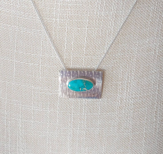 Kingman Mountain Turquoise. Nice oval shape set on textured metal. Hidden square tube bail.  All solid sterling silver.