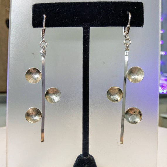 Sterling three disc dangle earrings on leverback wires.  Discs are patterned and beveled for depth.