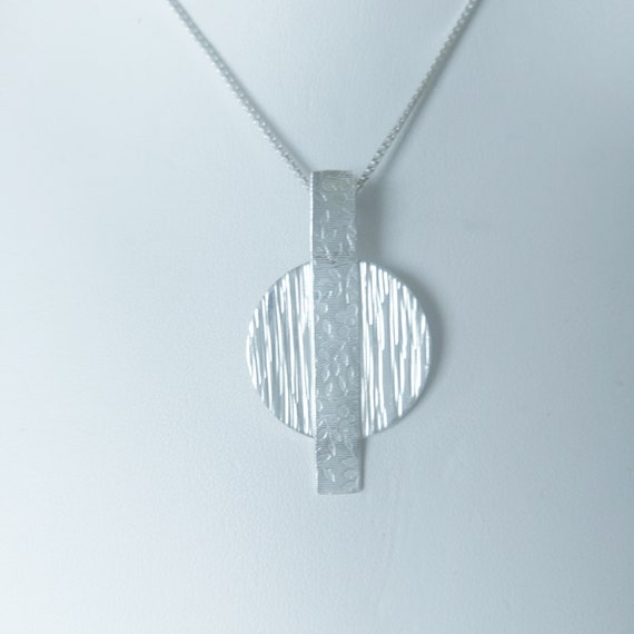 """Multi-textured pendant.  Hidden back bail on 18"""" sterling box chain. A great last minute add to a t-shirt and jeans!"""
