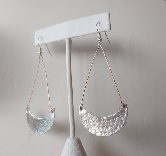 Sterling hammered half circle shaped textured earrings dangle from copper wire and french wires.