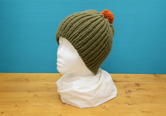 Olive green ribbed hat with orange bobble