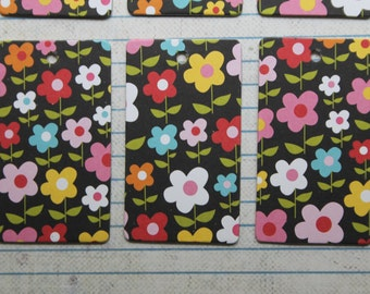 27 gift tags pink, white, yellow, blue red flowers on black paper over chipboard