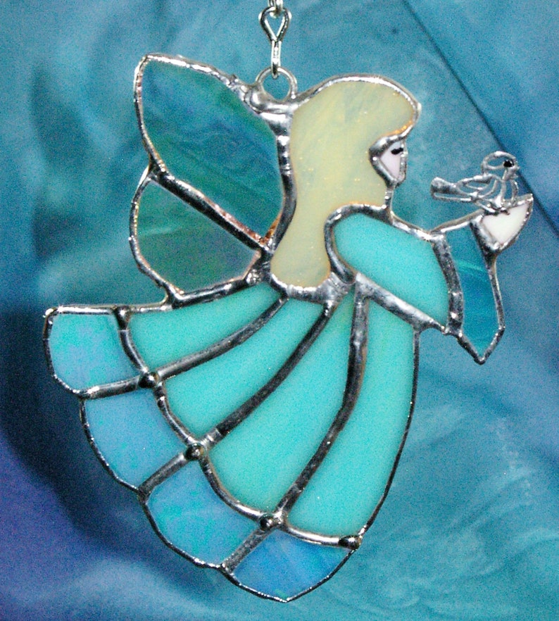 Handmade Blue Stained Glass Suncatcher Angel holding a bird on her hand.