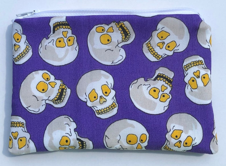 Skulls with Yellow Eyes Zipper Pouch  Purple Background. image 0