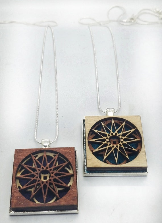 Abstract 1 pendant of plywood,redwood and felt set into stainless steel