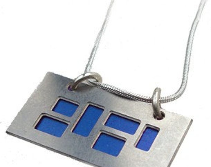 silver pendant with blue and Black cutouts