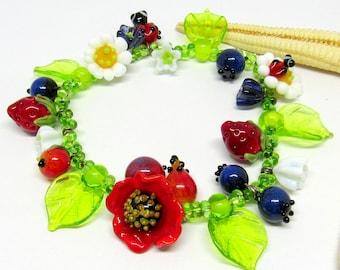bracelet with handmade lampwork beads, poppy, daisy, ladybug, flowers, lampwork