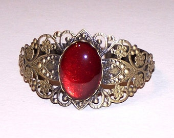 bronze bangle with deep red cabochon