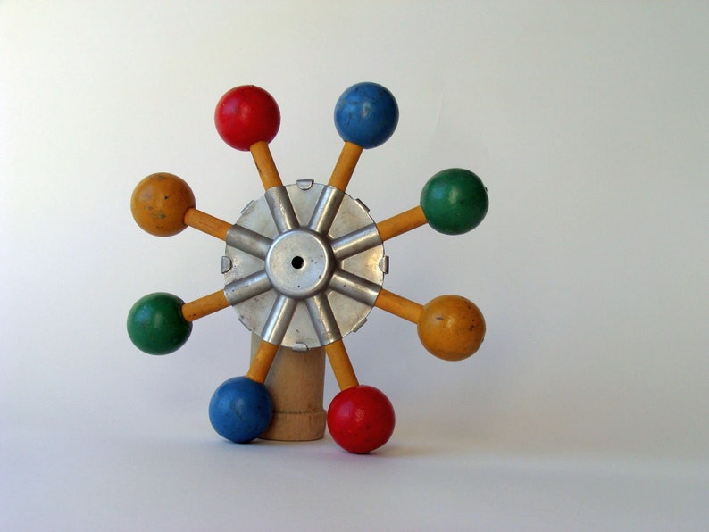 vintage wood and metal game or toy component with brighly painted balls which could easily be made to spin for hours of fun