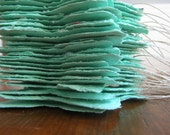 Sea foam green butterfly shaped favors made of plantable handmade paper embedded with perennial flower seeds