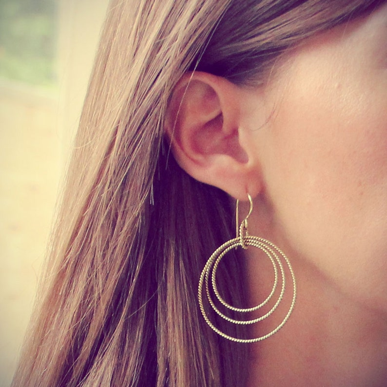 Gold Hoop Dangle Earrings circular hoops resting inside one image 0