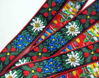 EDELWEISS & HEARTS Jacquard trim White, Blue, red, green, yellow on black. Red edges. Sold by the yard. 1 inch wide. 949(2)-A Bavarian trim
