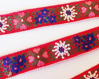 EDELWEISS & HEARTS Jacquard trim in white, blue, pink, green on red. Sold by the yard. 1 inch wide. V2773-B Bavarian trim
