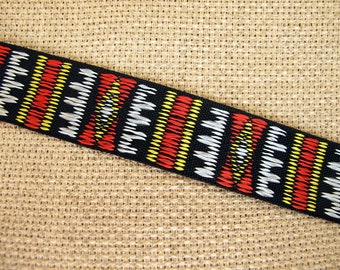 SADDLE RIDE Jacquard trim. Red, mustard yellow, slate grey on black. Sold by the yard. 1 inch wide. 2064-A. Colorful geometric trim ribbon