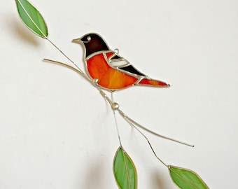 Baltimore Oriole stained glass bird suncatcher on tinned wire branch with green leaves.
