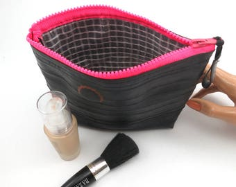 Recycled bicycle inner tube cosmetic pouch for men and woman, container, bag, withoriginal patch and neon pink zipper.