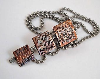 Layered pendant necklace.  Sterling silver with copper squares.  Stamping and textured designs.