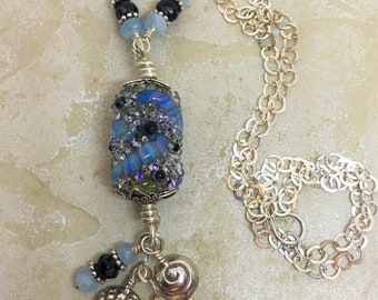 Sea shell charm statement necklace with glass focal bead and gemstones on long sterling silver cable chain. Thai silver charms and aquamarin
