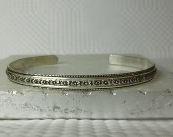 Horizontal flowers line this sterling silver cuff bracelet that has a very pretty fluted edge, part of the Love Collection
