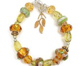 Bracelet with Lamp Worked and Large Hole Beads in Green, Amber, Olive Green and Silver with Magnetic Clasps
