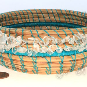 an asymmetrical pine needle basket with a Rosetta stone base Can hang two directions or sit on table. coiled basket Listening