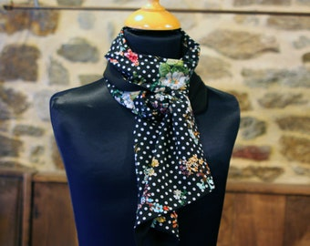Black woman in cotton and silk scarf with white dots and flowers. Slice of wool