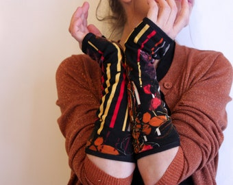 Long black flowers and multicolor striped mittens. Slice of wool
